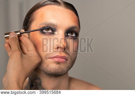 Unrecognizable man applying mascara to womanish man with beard while preparing him for theatrical performance
