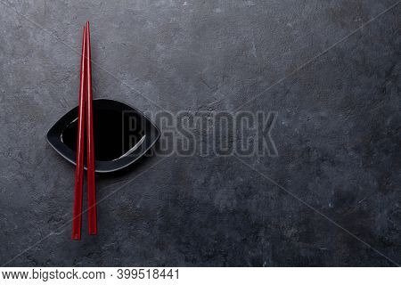 Stone table and chopsticks for your sushi and maki. Japanese food menu backdrop. Top view flat lay with copy space