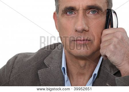 Serious man with glasses in hand
