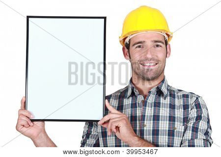 Construction worker holding up a blank bulletin board