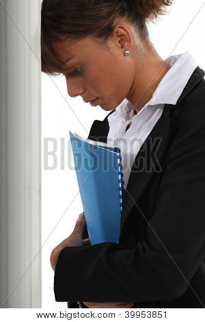 Frustrated woman leaning her head against a wall