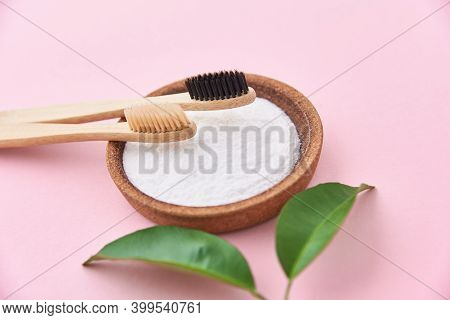 Two Wooden Bamboo Toothbrushes And Baking Soda On A Pink Background. Eco Friendly Toothbrushes, Zero