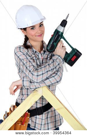 Female construction worker holding a battery-powered screwdriver