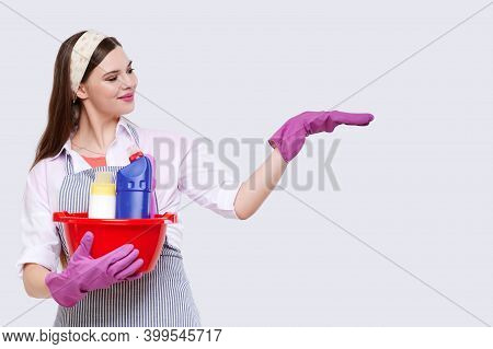 Housewife In Rubber Gloves Holding Basin With Detergent Bottles Holding Product, Isolated On White B