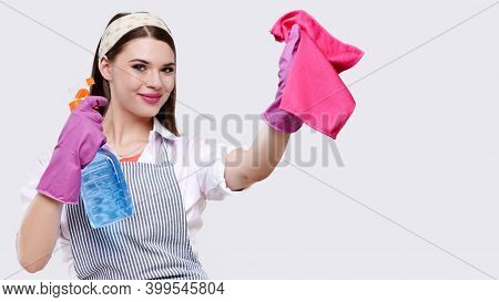 Young Smiling Housewife In Apron And Rubber Gloves Wipes The Surface With Red Rag And Using Cleaning