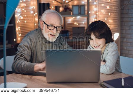 Grandfather And Grandson Are Watching Video At Laptop At Night. Grandfather Is Looking At His Grands