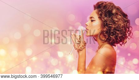 Beautiful glamorous woman in an expensive gold jewelry and with a glass of champagne in her hands on a festive background with lights. Jewelry. Make-up and hairstyle. Christmas and holiday.