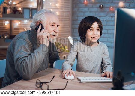 Grandfather And Grandson Are Playing Games On Computer At Night At Home. Granddad Is On Phone.