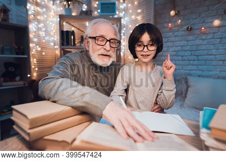Grandfather And Grandson Are Doing Homework At Night At Home. Granddad Is Helping Boy.