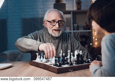 Grandfather And Grandson Are Playing Chess Together At Night At Home.