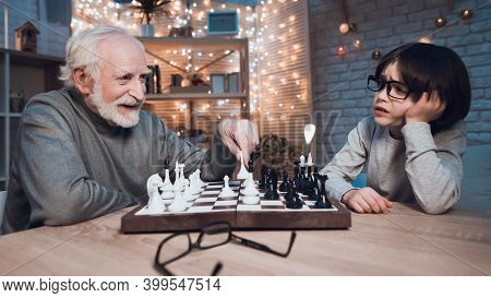 Grandfather And Grandson Are Playing Chess Together At Night At Home. Granddad Is Winning.