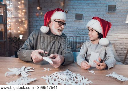 Grandfather And Grandson Are Making Christmas Decorations At Night At Home.