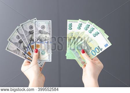 Female Hands Hold Fan With Dollars And Euros. Currency Converter Online Concept