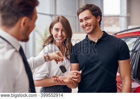Blurred Male Dealer Giving Key Of New Car To Excited Young Couple In Modern Auto Salon
