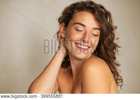 Beautiful smiling girl with freckles looking away on gray wall. Portrait of beauty young woman with nude shoulder and copy space. Natural beauty girl with silky curly hai, skin care and bodycare.