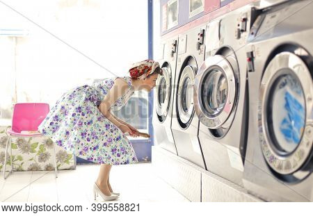 young woman in a room of public washing machines