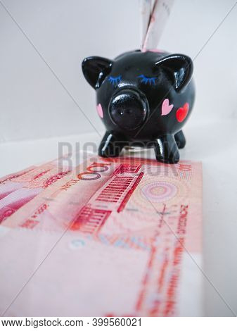 Black Piggy Bank Standing Next To Chinese 100 Rmb Banknotes On A White Wooden Background. The Pig Sy