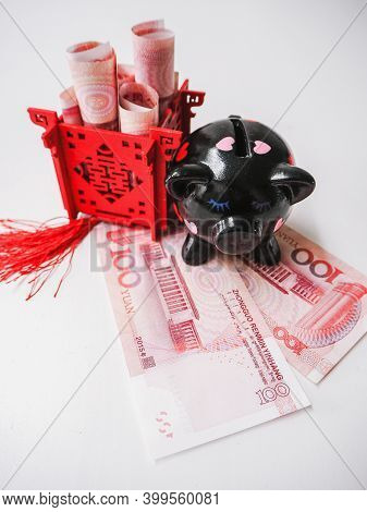 Black Piggy Bank And Chinese Pavilion Filled With Banknotes, Standing On Chinese 100 Renminbi Notes