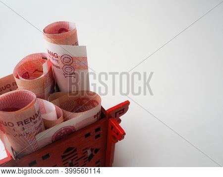 Miniature Chinese Pavilion In Bright Red Filled With Chinese 100 Renminbi Banknotes Against A White