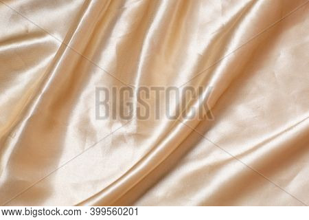 The Texture Of The Fabric Silk. Beige Fabric Pleated. Close-up. Can Be Used As A Background.
