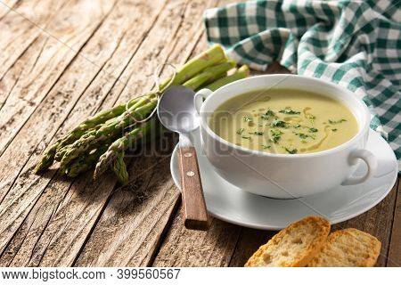 Fresh Green Asparagus Soup On Rustic Wooden Table. Copy Space