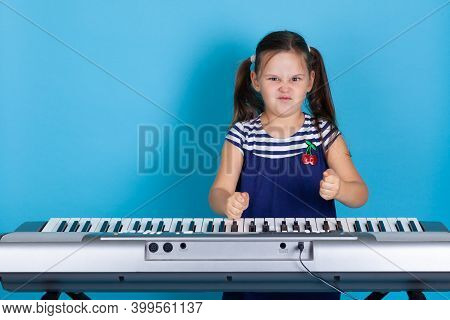 Mock Up Scowling Girl Banging Her Fists On Synthesizer Keys, Hating Classical Music, Isolated On Blu