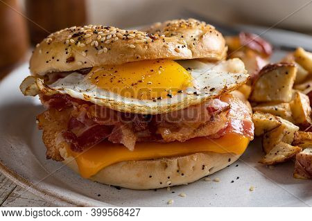 Closeup Of A Breakfast Sandwich On A Bagel With Fried Egg, Bacon And Cheese