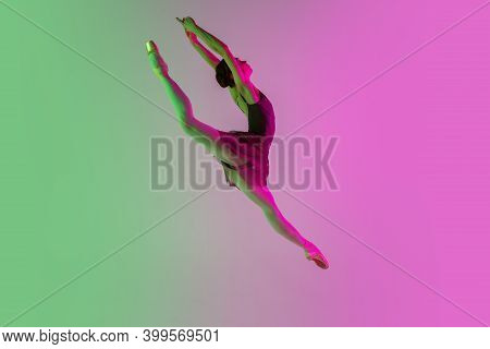 Flying. Young And Graceful Ballet Dancer Isolated On Gradient Pink-green Studio Background In Neon.