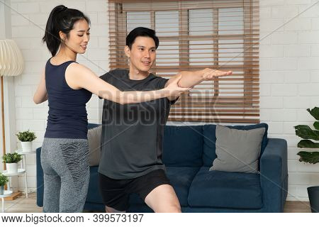 Healthy Young Asian Couple Exercises In Home And Wife Teaching Her Husband For Exercise In Covid-19