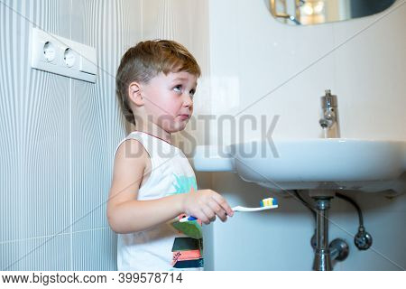 Little Boy Stands Near The Sink With A Toothbrush.