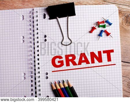The Word Grant Is Written In A Notebook Near Multi-colored Pencils And Buttons On A Wooden Backgroun