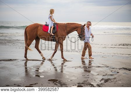 Little Pretty Girl On A Horse. Father Leading Horse By Its Reins On The Beach. Horse Riding By The S