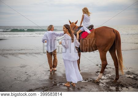 Little Girl On A Horse. Father Leading Horse By Its Reins On The Beach. Horse Riding By The Sea. Mot