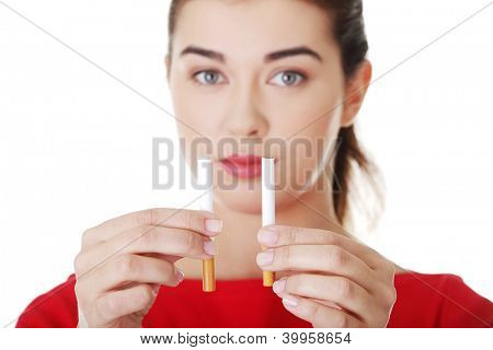 Young woman holding in one hand classic cigarette and in other electronic cigarette