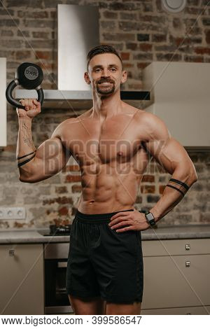 A Happy Muscular Man With A Beard Is Pushing A Black Weight In His Apartment. A Bodybuilder With A N
