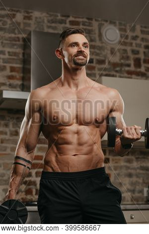 A Muscular Man With A Beard Is Training His Biceps With Dumbbells In His Apartment. A Happy Bodybuil