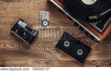 Old Vinyl Record Player, Video Cassettes, Audio Cassette, Old-fashioned Film Camera On The Floor. Re