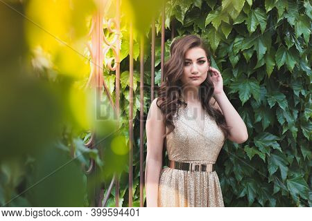 Beautiful Teen Girl In Glamorous Golden Dress. Prom Fashion