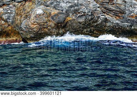 Sea Waves Crash Against A Natural Granite Cliff Wall. Beautiful Sea Wallpaper With Dark Blue Water,