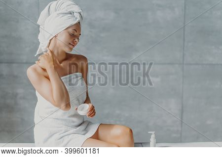 Satisfied Spa Woman Sits In Profile Applies Body Cream For Perfect Skin, Enjoys Pampering And Beauty