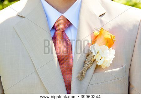A groom in a light-colored suit is ready for his wedding day in formal attire with a boutineer on his jacket lapel. poster