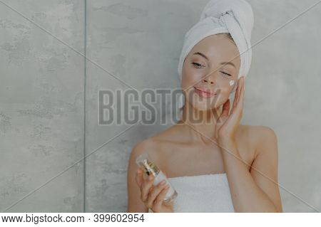 Lovely European Woman Applies Facial Moisturizer Holds Bottle Of Body Lotion, Has Healthy Skin, Well