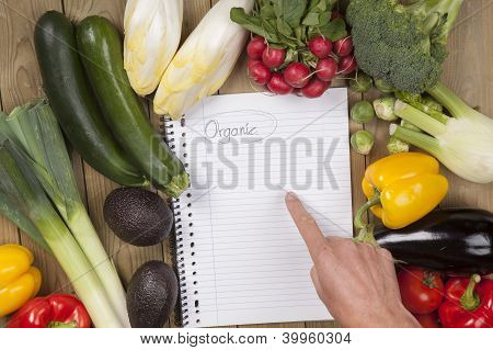 Hand pointing on book with vegetables over surface