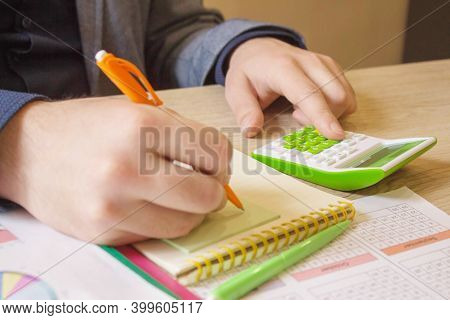 Hand Of Young Man Using Calculator For Calculating Family Budget Cost Bills On Desk In Home Office,