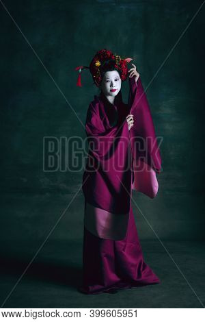 Blooming. Young Japanese Woman As Geisha Isolated On Dark Green Background. Retro Style, Comparison