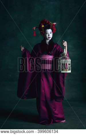 Birds Cage. Young Japanese Woman As Geisha Isolated On Dark Green Background. Retro Style, Compariso