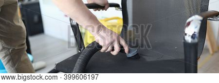 Close-up Of Person Cleaning Black Comfy Chair Using Compact Vacuum Cleaner. Place For Sitting. Man C