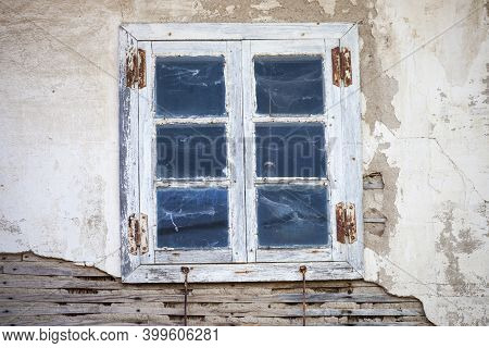 Discolored Bluish Wood Window With Six Panes, Four Rusty Hinges, In A Dirty, Chipped Wall. Galicia,