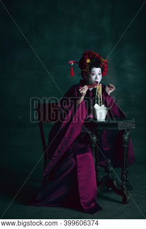 Tasty Fastfood. Young Japanese Woman As Geisha Isolated On Dark Green Background. Retro Style, Compa