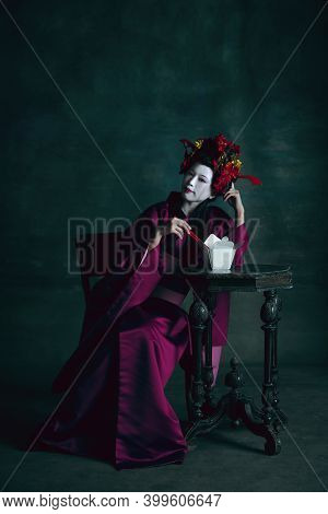 Food Tastes Good. Young Japanese Woman As Geisha Isolated On Dark Green Background. Retro Style, Com